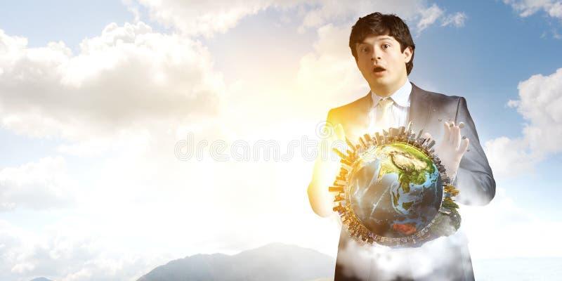 Ung affärsman som står förvånad och rymmer jordmodellen Blandat massmedia royaltyfri bild