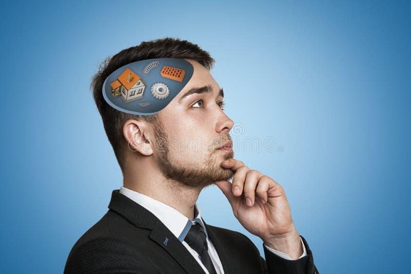 Ung affärsman som tänker med det vita huset, kugghjulhjul, tegelstenar, spolevårar i hans huvud på blå bakgrund arkivbild