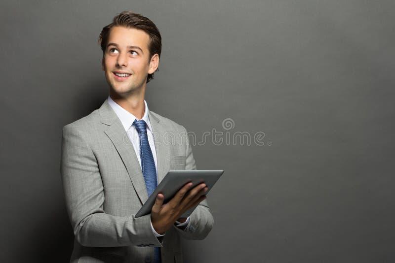 Ung affärsman som tänker, medan rymma en minnestavla royaltyfri foto