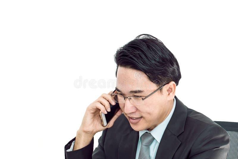 Ung affärsman som talar med den smarta telefonen Honom som ser le arkivfoto