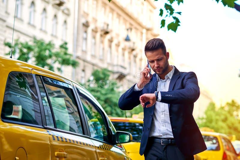 Ung affärsman som talar på en telefon och väntar på hans taxi arkivfoton