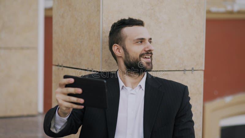 Ung affärsman som talar på minnestavladatoren som har video pratstund med hans fru Affärsman som använder app för att ha videoen royaltyfri bild