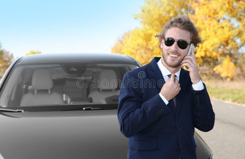 Ung affärsman som talar på telefonen nära den moderna bilen royaltyfria foton