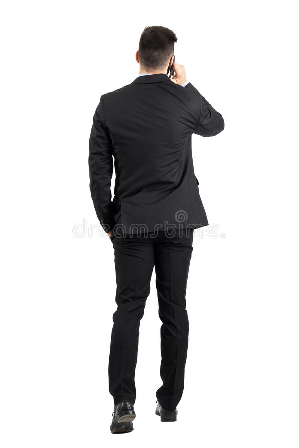 Ung affärsman som talar på telefonen som bort går bakre sikt royaltyfri foto