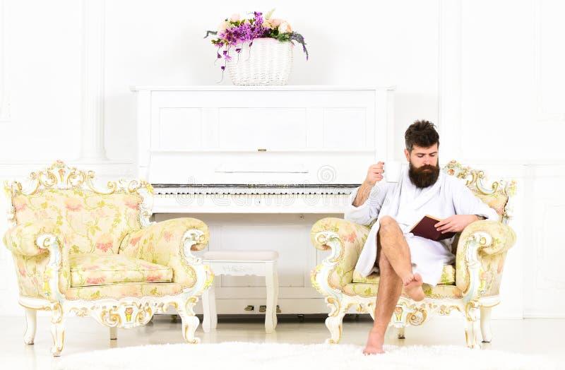 Ung affärsman som tycker om hans morgonkaffe för arbete Koncentrerad grabb som läser en bok, medan sitta i fåtölj arkivfoto