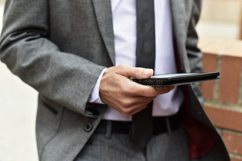 Ung affärsman som utomhus använder en minnestavla arkivbild