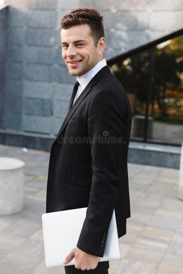 Ung affärsman som utomhus går på gatan med bärbar datordatoren arkivfoto
