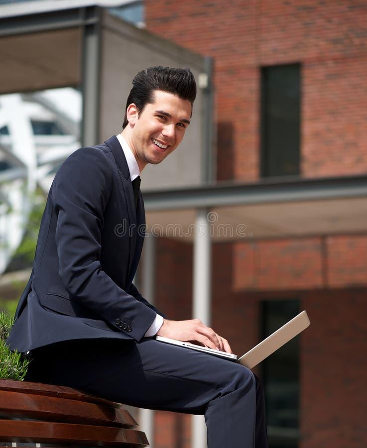 Ung affärsman som utomhus ler med bärbara datorn royaltyfri fotografi