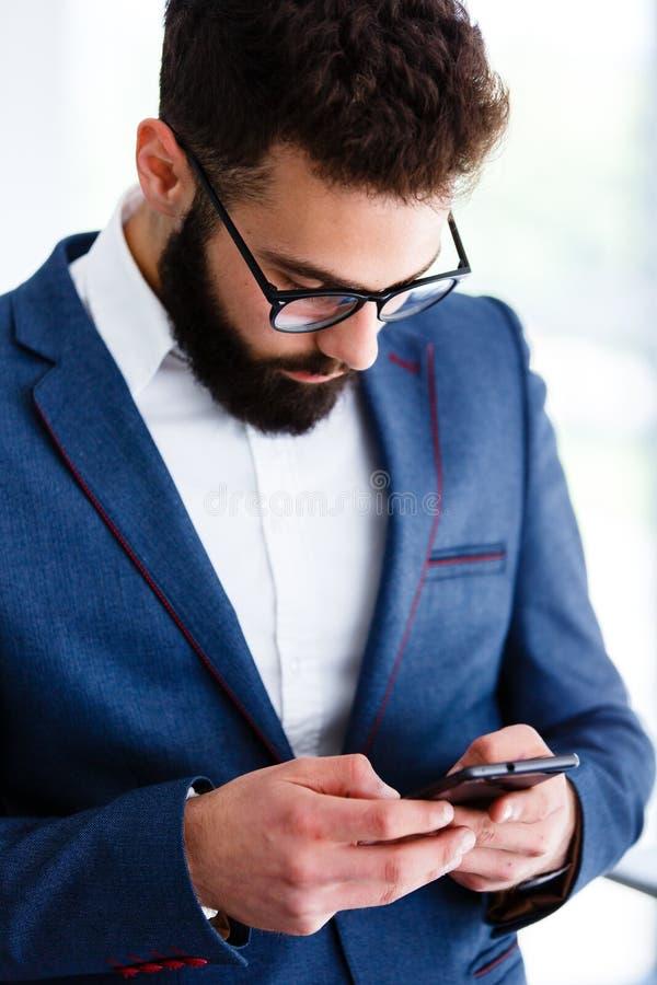Ung affärsman Using Mobile Phone på arbetsplatsen fotografering för bildbyråer