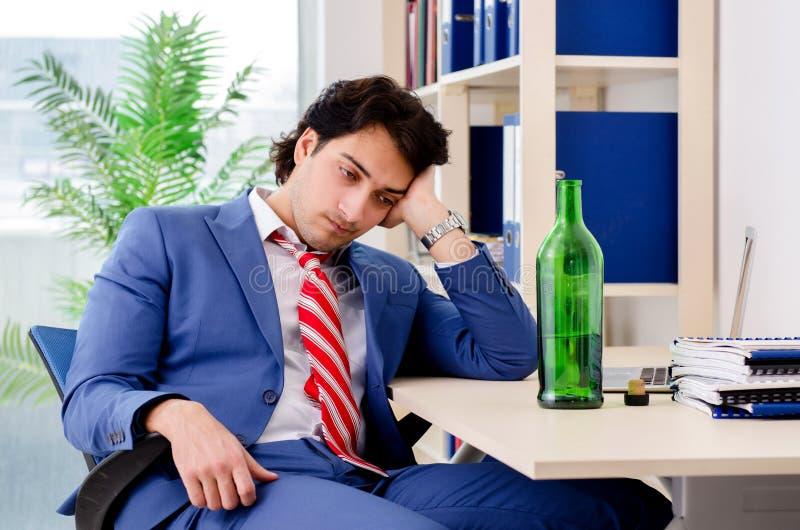 Ung affärsmananställd som dricker i kontoret royaltyfria bilder