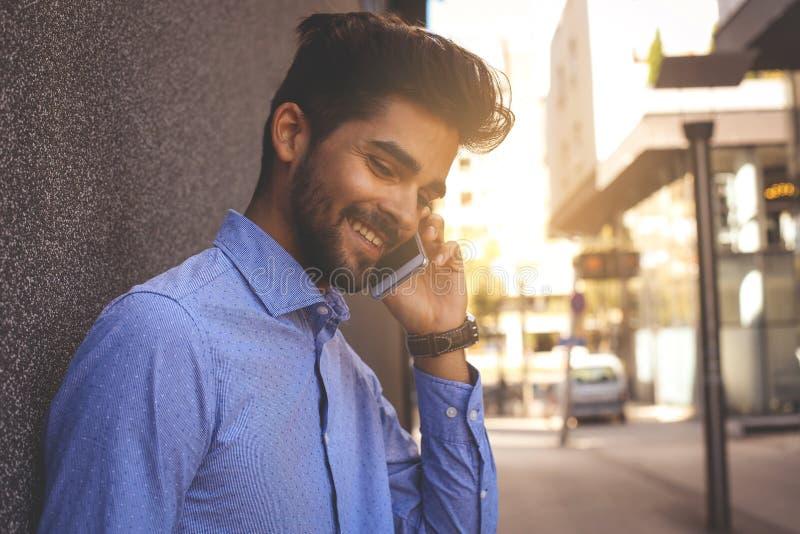 Ung affärsmanbenägenhet mot väggen som talar på den smarta telefonen S fotografering för bildbyråer