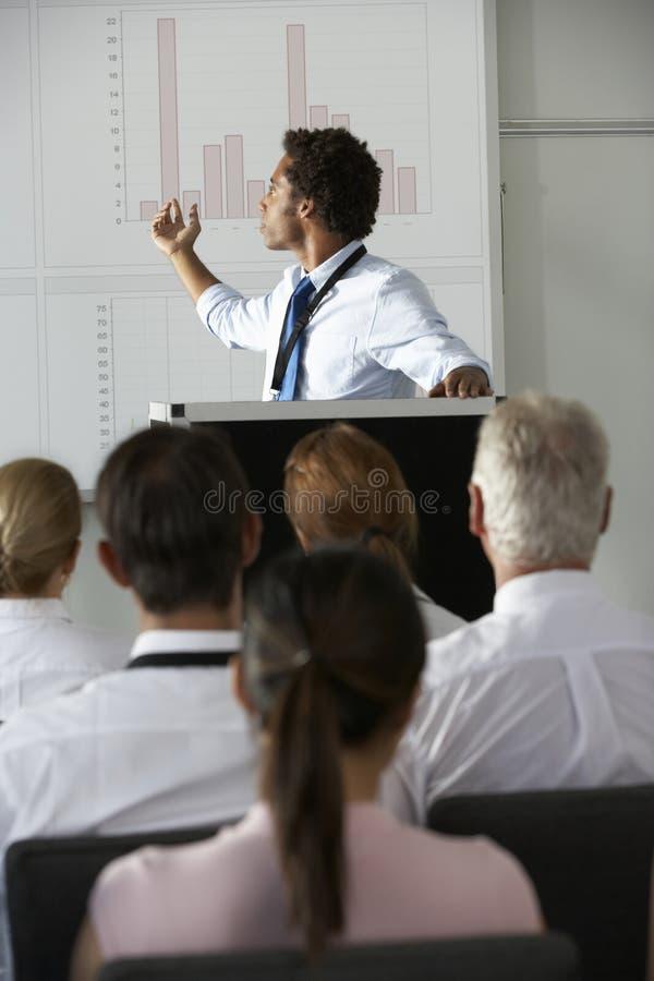 Ung affärsmanDelivering Presentation At konferens royaltyfri bild