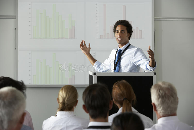 Ung affärsmanDelivering Presentation At konferens arkivfoto