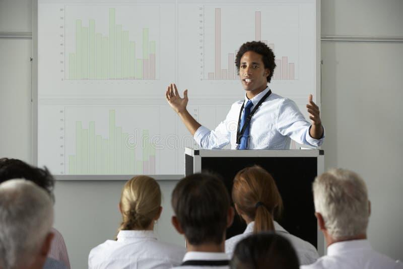 Ung affärsmanDelivering Presentation At konferens royaltyfri foto