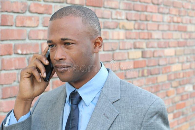 Ung affärsmangråt på telefonen Förarga affärstelefonkonversation Isolerat på bakgrund för tegelstenvägg arkivbilder