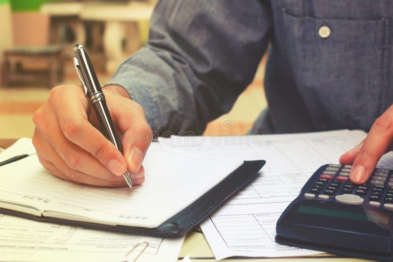 Ung affärsmanhandstil och gör anmärkningen om kostnad arkivfoton