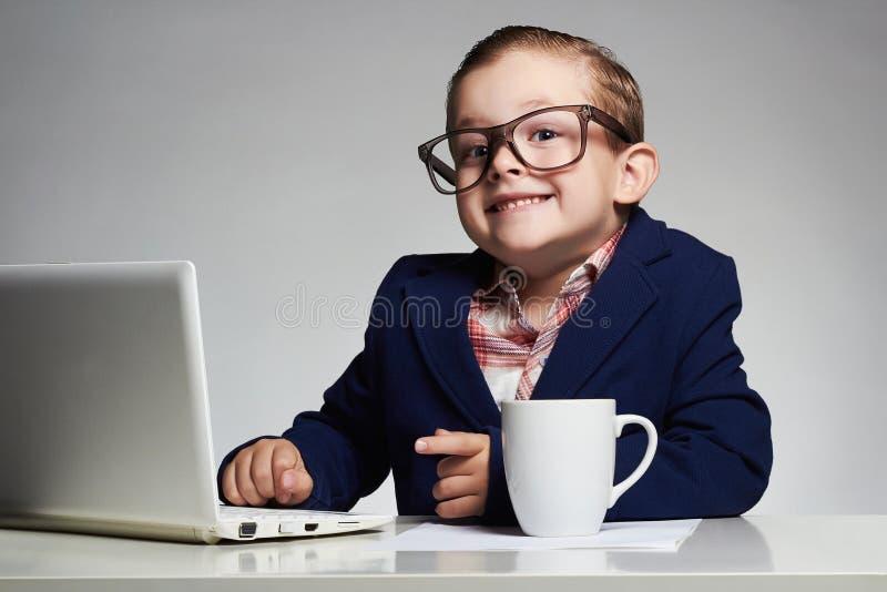 Ung affärspojke le barnet i exponeringsglas litet framstickande i regeringsställning arkivbild