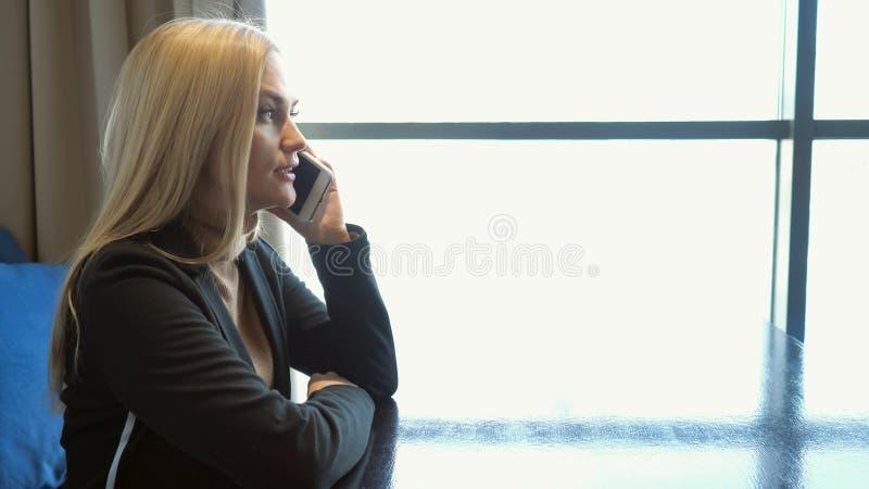 Ung aff?rskvinna i dr?kten som sitter p? tabellen i kaf?t som talar p? mobiltelefonen fotografering för bildbyråer