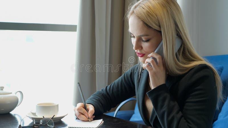 Ung aff?rskvinna i dr?kten som sitter p? tabellen i kaf? royaltyfria foton