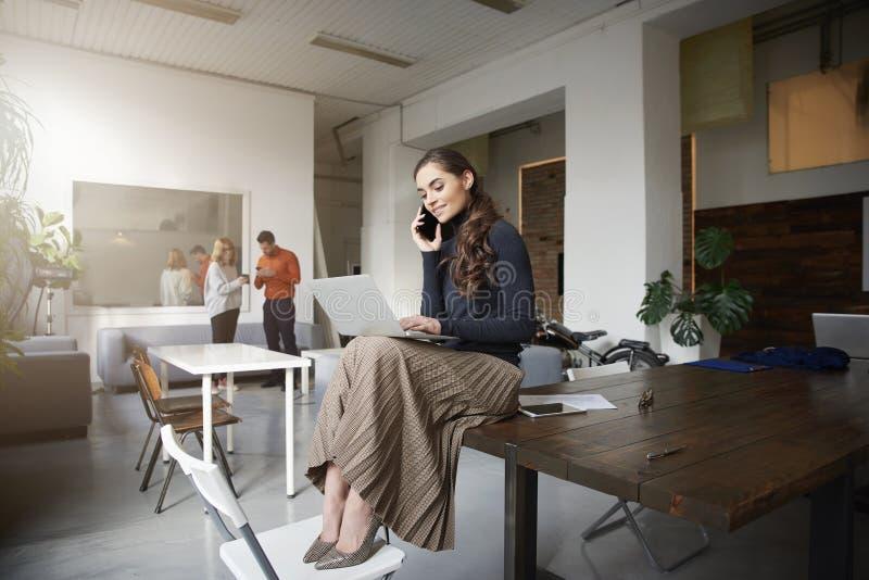 Ung aff?rskvinna som g?r en appell, medan sitta p? skrivbordet och att arbeta f?r kontor royaltyfri foto