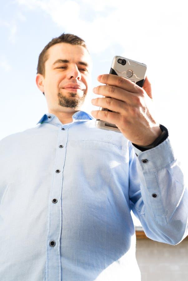 Ung aff?rsman som anv?nder mobiltelefonen som skrattar och skriver meddelandet arkivfoto