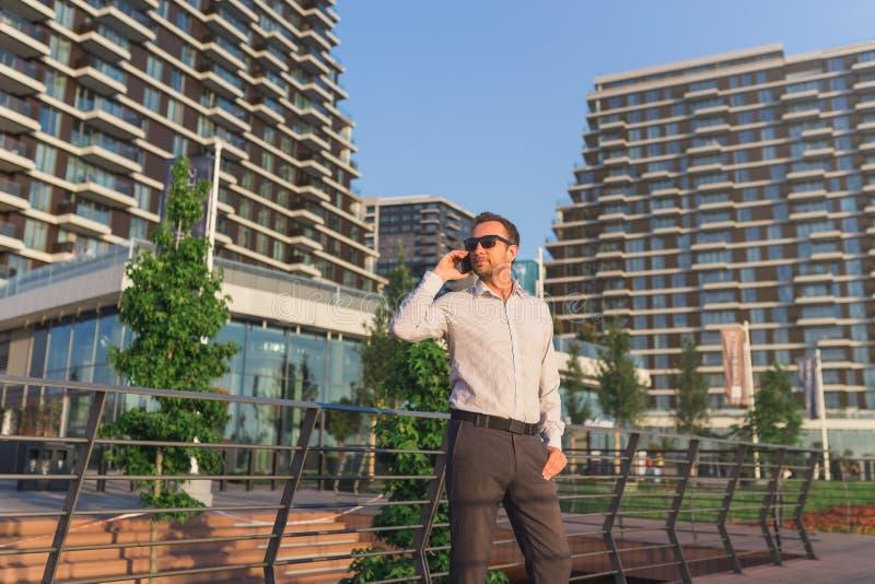 Ung aff?rsman som utomhus talar p? hans telefon fotografering för bildbyråer