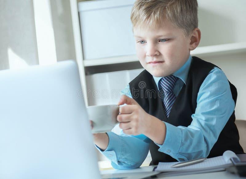 Ung aff?rspojke som arbetar p? b?rbara datorn som rymmer den vita koppen kaffe eller varmt te Roligt litet framstickande i regeri arkivfoton