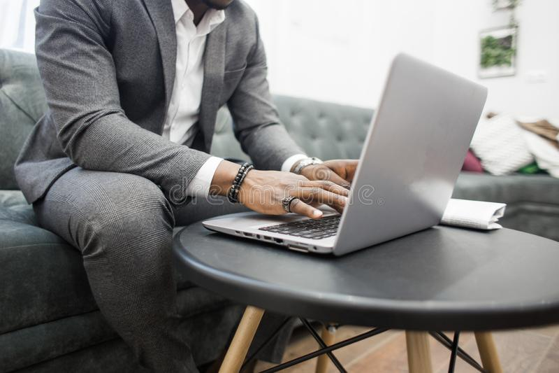 Ung afrikansk amerikanaffärsman i en grå dräkt som arbetar bak en bärbar dator arkivfoto