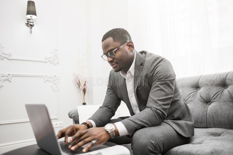 Ung afrikansk amerikanaffärsman i en grå dräkt som arbetar bak en bärbar dator royaltyfri bild