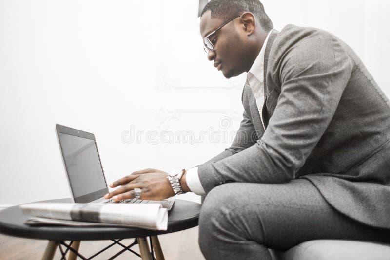 Ung afrikansk amerikanaffärsman i en grå dräkt som arbetar bak en bärbar dator royaltyfria bilder