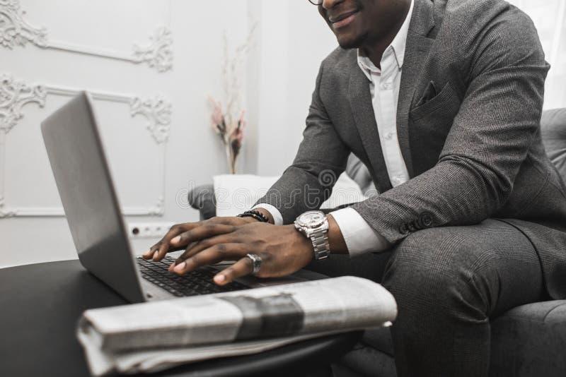 Ung afrikansk amerikanaffärsman i en grå dräkt som arbetar bak en bärbar dator arkivbilder