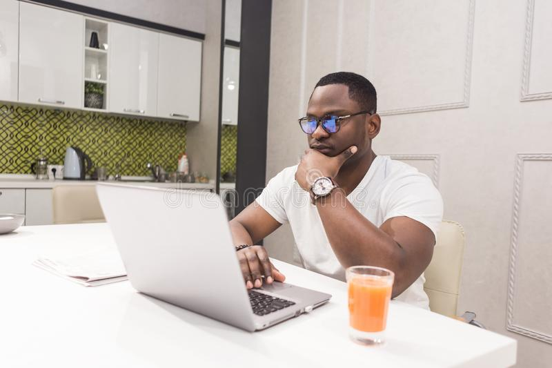 Ung afrikansk amerikanaffärsman som arbetar på en bärbar dator i köket i en modern inre royaltyfria foton