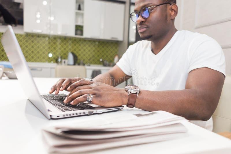 Ung afrikansk amerikanaffärsman som arbetar på en bärbar dator i köket i en modern inre fotografering för bildbyråer