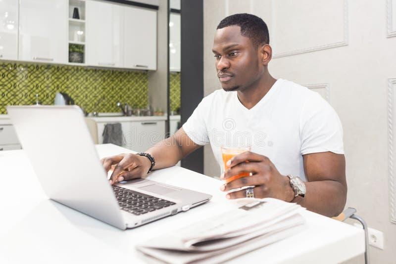 Ung afrikansk amerikanaffärsman som arbetar på en bärbar dator i köket i en modern inre arkivfoton