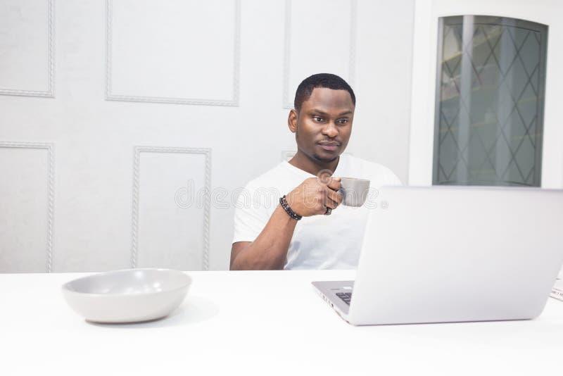 Ung afrikansk amerikanaffärsman som arbetar på en bärbar dator i köket i en modern inre arkivfoto