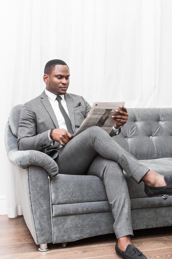 Ung afrikansk amerikanaff?rsman i en gr? dr?kt som l?ser en tidning, medan sitta p? en soffa royaltyfri fotografi