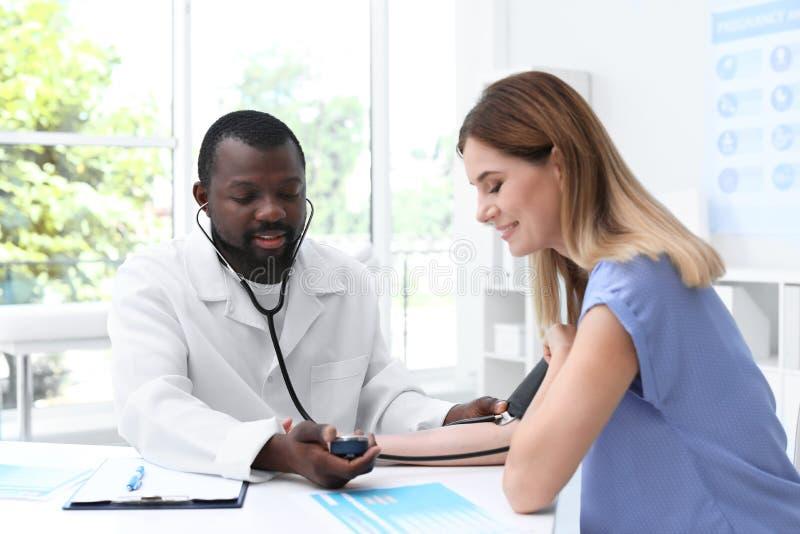 Ung afrikansk amerikandoktor som kontrollerar tålmodig puls och blodtryck för ` s royaltyfri fotografi