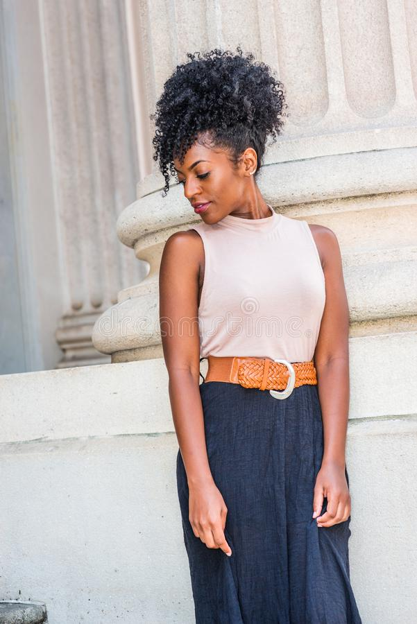 Ung afrikansk amerikanflicka med den afro frisyren, vitt örapärlstift, bärande sleeveless överkant för ljus färg som är mörk - or royaltyfri bild