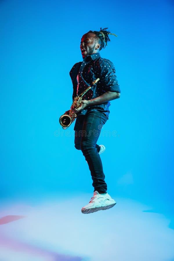 Ung afrikansk amerikanjazzmusiker som spelar saxofonen arkivfoton