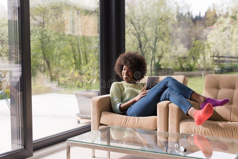 Ung afrikansk amerikankvinna hemma som använder den digitala minnestavlan royaltyfria bilder