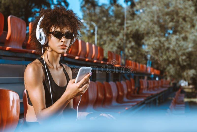 Ung afrikansk amerikankvinna i sportive dress som lyssnar till musik arkivbilder