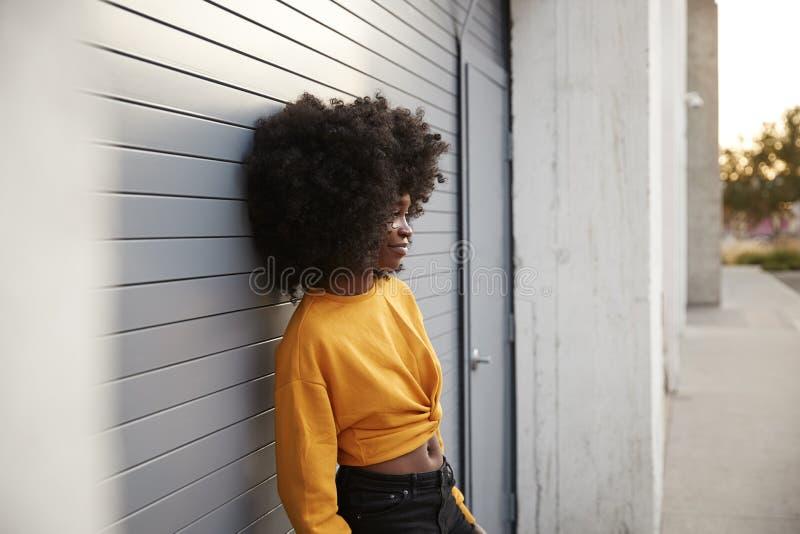 Ung afrikansk amerikankvinna med afroen som lutar i gatan mot gråa säkerhetsslutare, sidosikt royaltyfria foton