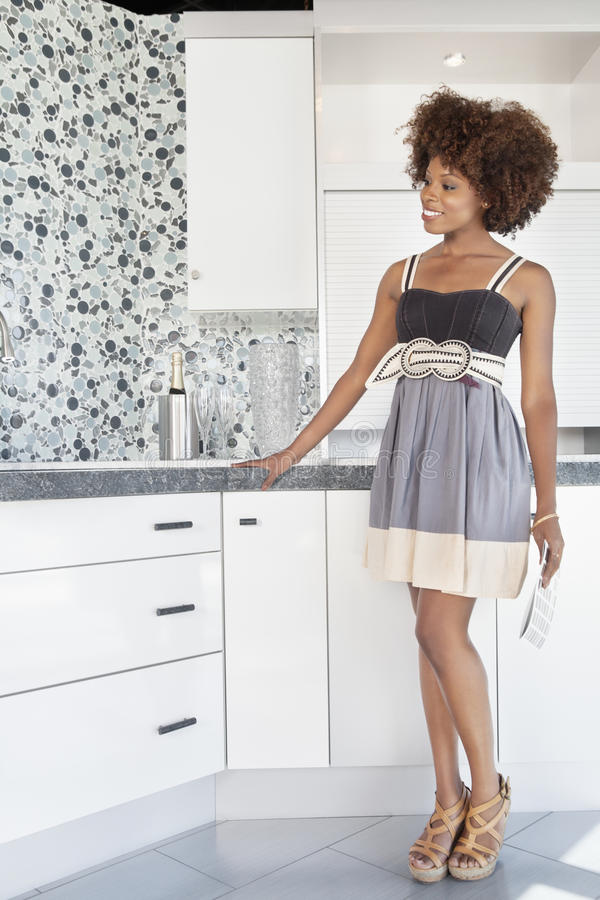 Ung afrikansk amerikankvinna som beundrar den planlagda väggen i nytt huskök arkivfoton