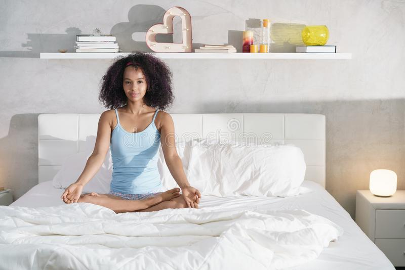 Ung afrikansk amerikankvinna som gör yoga i säng efter sömn royaltyfria bilder
