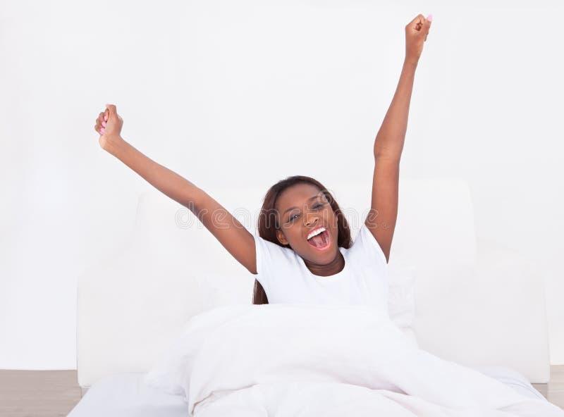 Ung afrikansk amerikankvinna som hemma sträcker i säng arkivbilder