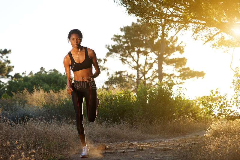 Ung afrikansk amerikankvinna som joggar i natur arkivfoton