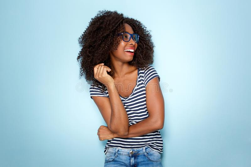 Ung afrikansk amerikankvinna som ler med exponeringsglas på blå bakgrund arkivbild