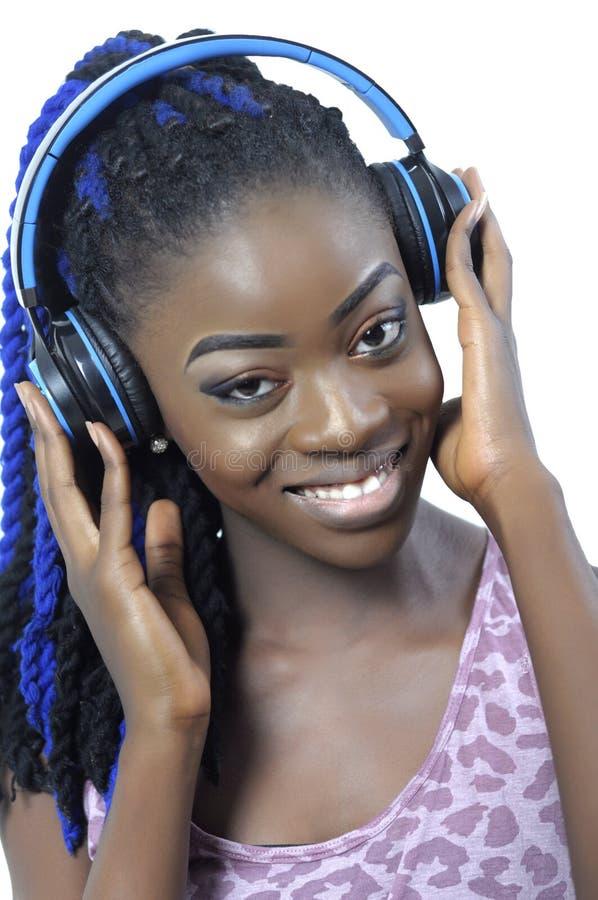 Ung afrikansk amerikankvinna som lyssnar till musik arkivfoto
