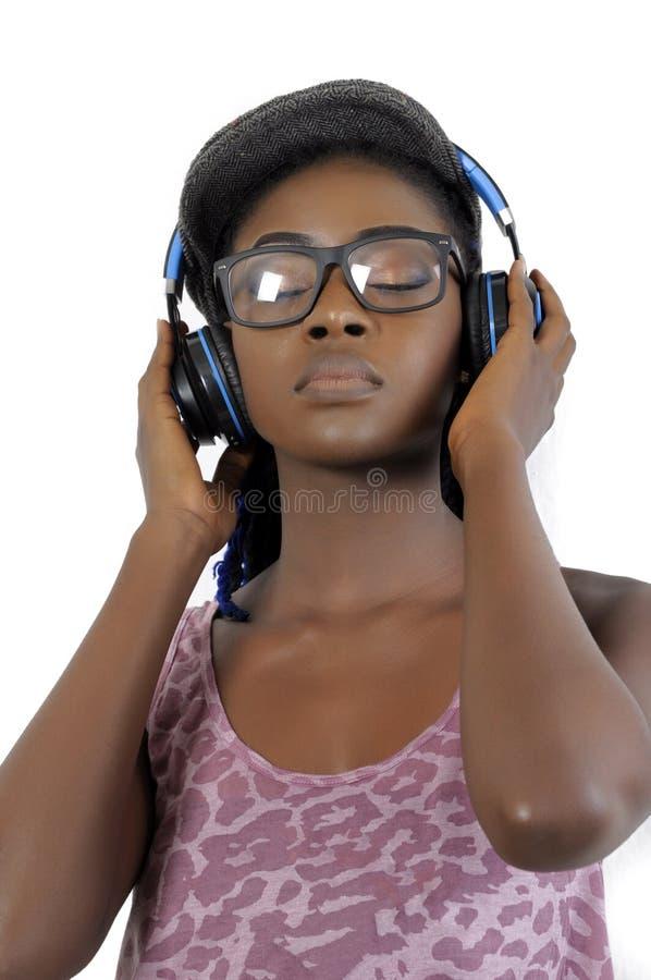 Ung afrikansk amerikankvinna som lyssnar till musik royaltyfri foto