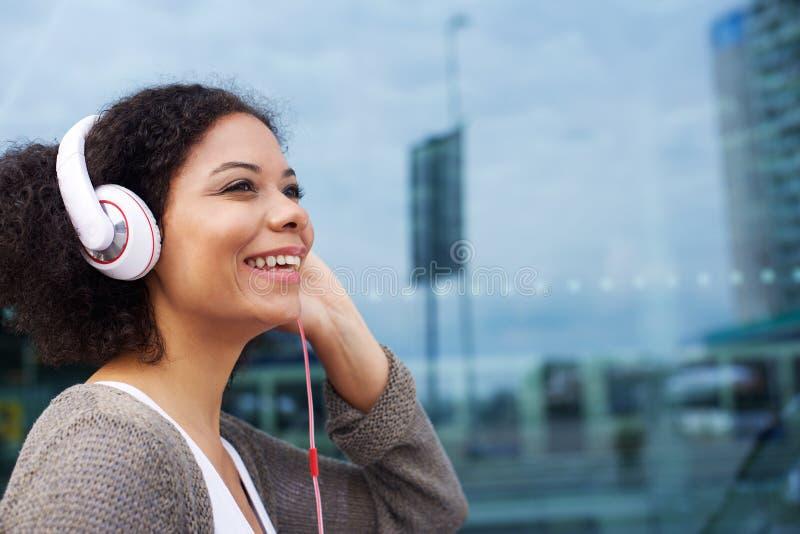 Ung afrikansk amerikankvinna som lyssnar till musik på hörlurar arkivfoto